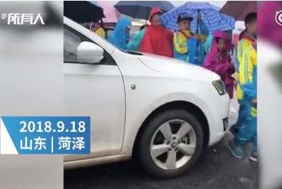 菏泽女司机学校门口驾车抵着孩子蹭路